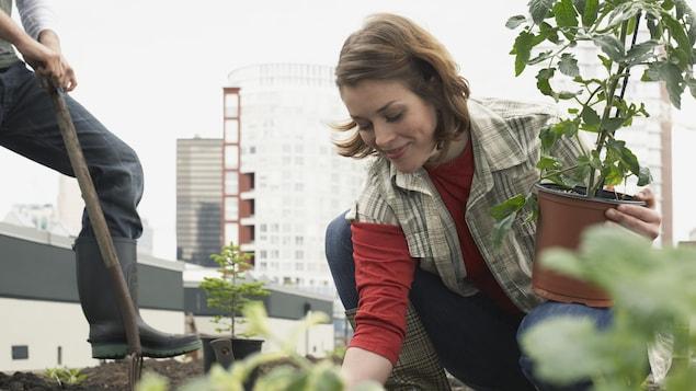 Une jeune femme jardine sur un toit.