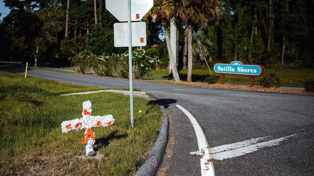 Une croix est plantée dans le gazon en bordure d'une route.