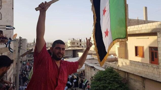 Ahmed Al Khaled brandit un drapeau syrien.