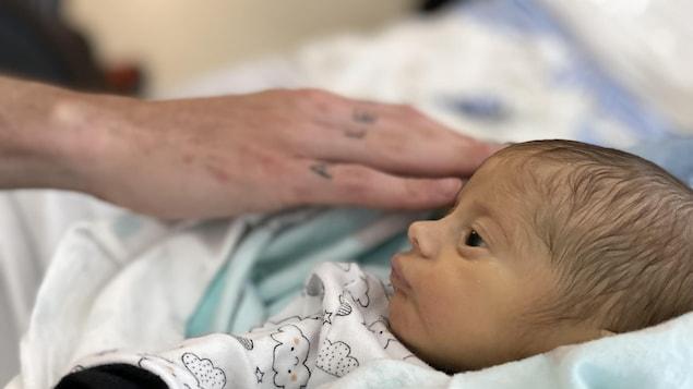 Une main se pose à côté du bébé dans un lit d'hôpital.