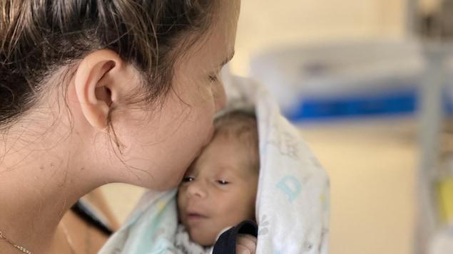 Une mère embrasse son fils sur le front.