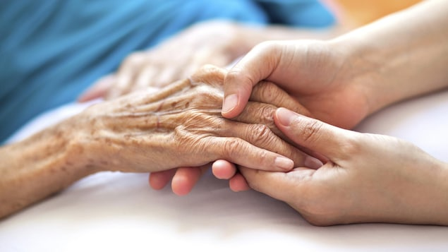 Les deux mains d'une personne relativement jeune tiennent celle d'une personne âgée.