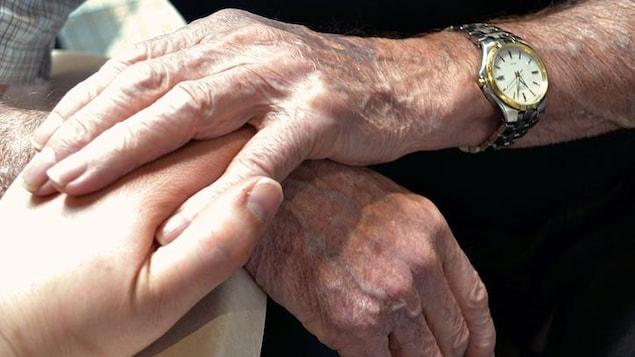 Deux personnes, l'une plus jeune, l'autre plus vieille et portant une montre, se tiennent affectueusement les mains.