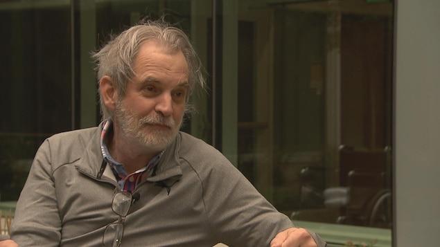 Un homme assis en extérieur, le visage serein et apaisé.