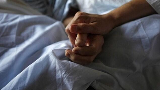 Une personne tient la main d'un homme couché dans un lit.