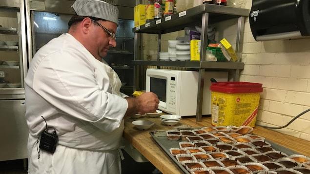 Gérard suit une formation d'aide cuisinier de 33 semaines offerte par l'organisme de réinsertion sociale Resto Plateau. Sur la photo il s'apprête à servir de petit gâteaux.
