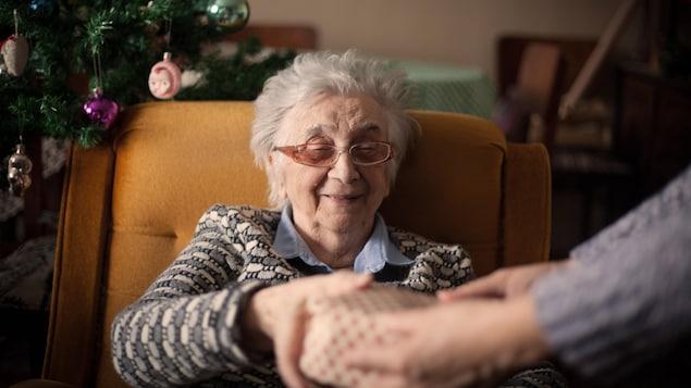 Une vieille dame reçoit un cadeau devant un sapin.