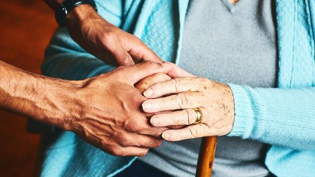 Une main d'homme tient la main d'une femme âgée tenant une canne.