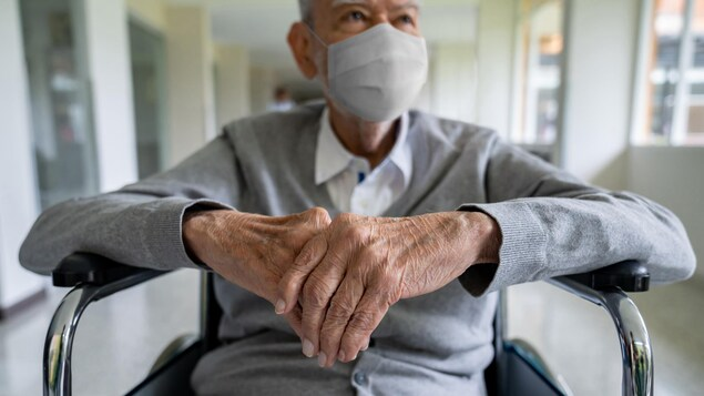 Un aîné assis dans un couloir, masqué.