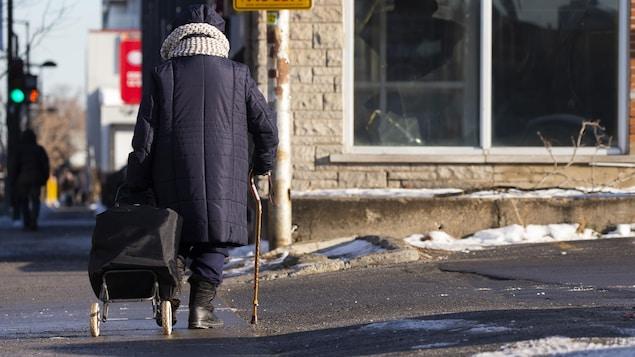 Une personne âgée marche avec une canne en tirant un chariot dans la rue Ontario à Montréal.