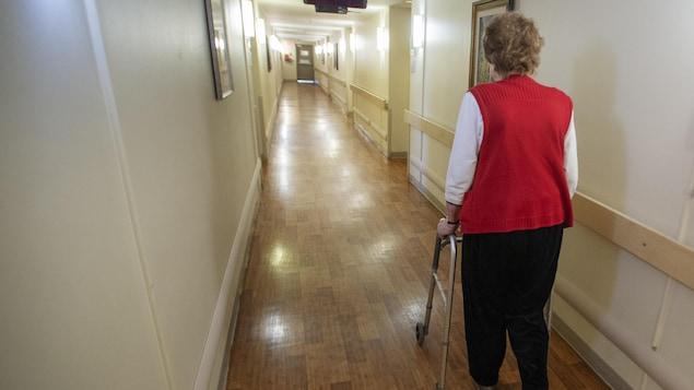 Une dame âgée marche avec l'aide d'un déambulateur.