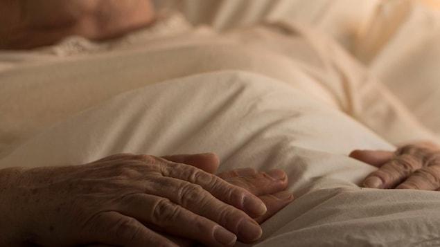 Une personne âgée est alitée. Quelqu'un lui tient la main.