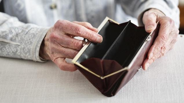 Une personne aînée fouille dans un porte-monnaie vide.