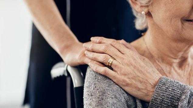 Une dame âgée sur un fauteuil roulant avec une personne debout.