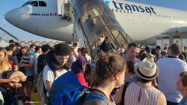 Photo de passagers sur le tarmac près d'un avion et d'autres qui descendent de l'appareil par un escalier.