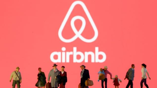 Des figurines représentant des voyageurs et des touristes devant un logo d'Airbnb.