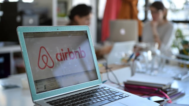 Sur un ordinateur portable, une fenêtre pour réserver un logement sur Airbnb est ouverte.