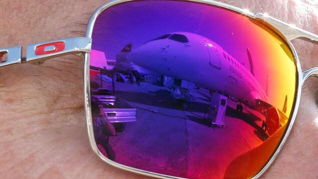 Un avion est visible dans le reflet des lunettes d'un visiteur au salon aéronautique Le Bourget.