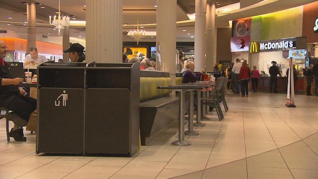Des gens mangent attablés dans une aire de restauration d'un centre commercial.