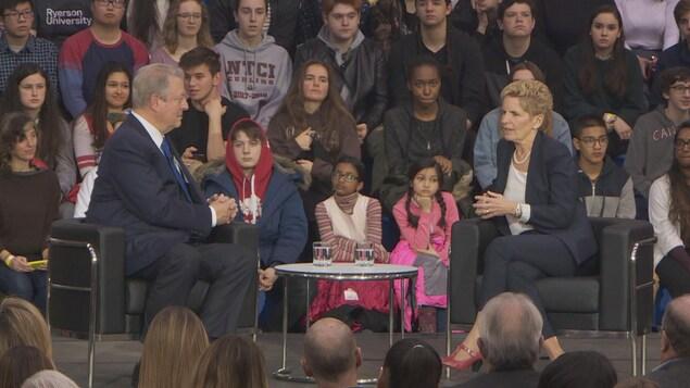 Photo d'Al Gore et de Kathleen Wynne assis dans des fauteuils sur un plateau devant des étudiants.