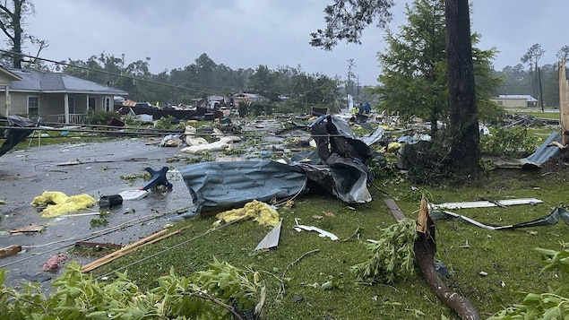 Des débris d'arbres et de maisons jonchent le sol.