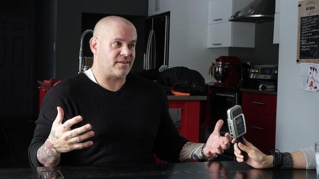 Un homme vêtu de couleurs sombres et devant une table, accorde une entrevue à la radio.