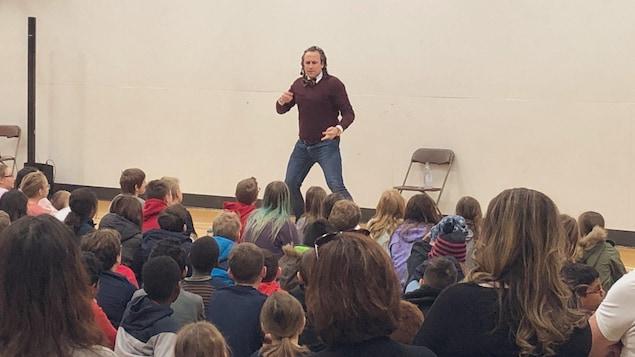 Le conférencier s'adresse de façon théâtrale à une foule d'élèves.