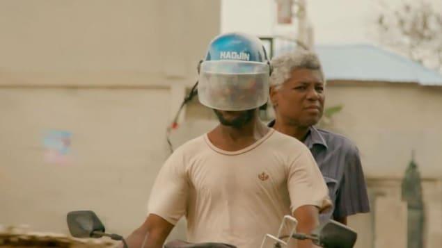 Deux hommes sont sur un cyclomoteur. L'un porte un casque avec une visière.