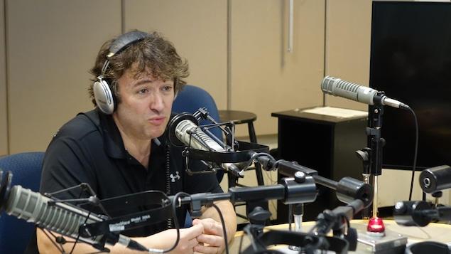 Un homme avec des écouteurs est assis derrière un micro de radio.