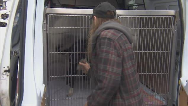 Un homme avec une longue barbe flatte un chien noir et blanc qui est dans une cage.