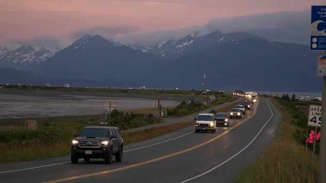 A line of cars is shown on a road with cloudy mountains in the background.