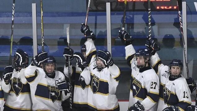 Des joueurs sur le banc des joueurs les bâtons dans les airs pour célébrer la victoire.