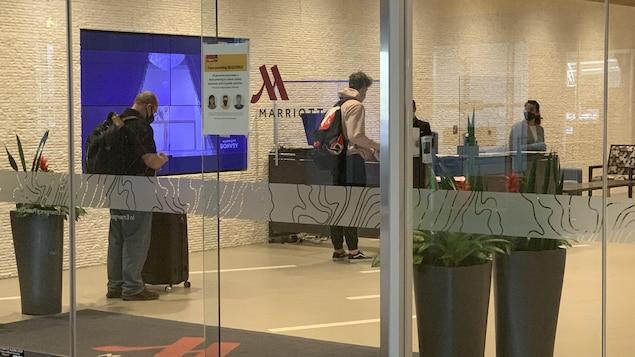 Des voyageurs attendent en ligne pour pouvoir s'enregistrer à l'hôtel Marriott de l'aéroport de Calgary.
