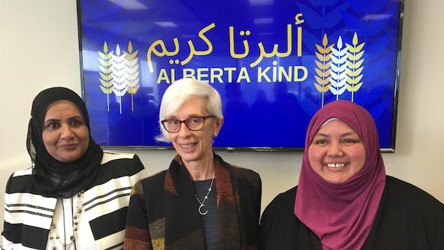 Trois femmes dont deux voilées devant une affiche bleue et dorée avec le slogan Alberta Kind en anglais et en arabe