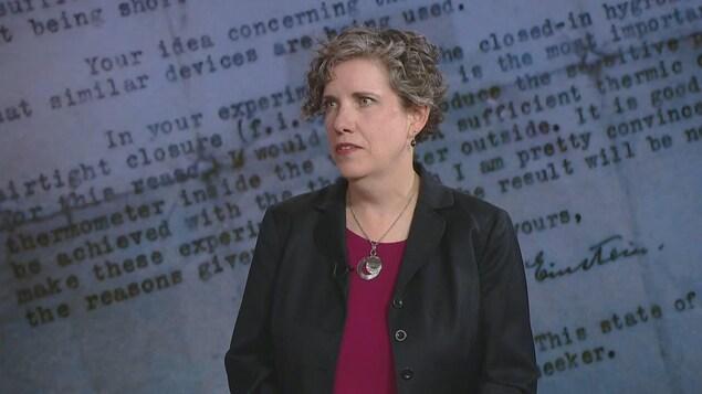 Dans l'image il y a Allison Wagner, directrice des manuscrits et livres rares de l'Université de Calgary debout en tailleur noir sur une tenue rouge au vin.