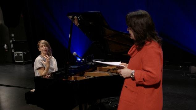 Une femme se tenant derrière un piano à queue sur scène discute avec une autre femme qui tient des partitions.
