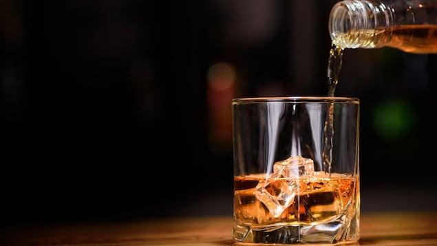 De l'alcool est versé d'une bouteille dans un verre