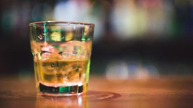 Gros plan sur un verre avec de l'alcool sur des cubes de glace déposé sur une table en bois.