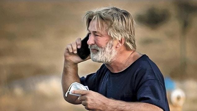 Alec Baldwin tient un téléphone dans une main et un masque dans l'autre.