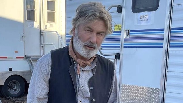 Alec Baldwin arbore un costume de cowboy dont la chemise est maculée de faux sang.