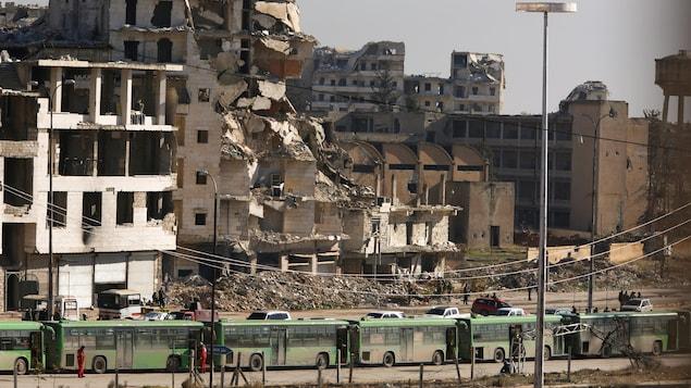 Plusieurs autobus verts sont stationnés devant un immeuble en ruine dans la ville syrienne d'Alep.