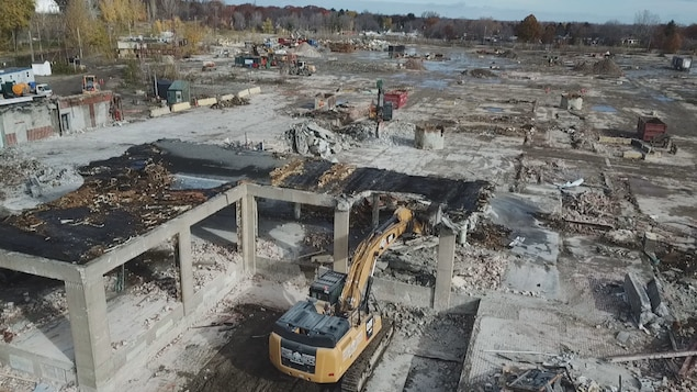 Des pelles mécaniques détruisent une usine abandonnée.