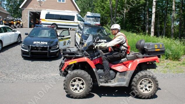 Un homme sur un quad devant un déploiement policier.