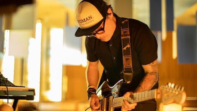 Un homme joue de la guitare électrique.