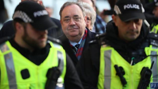 L'ancien premier ministre d'Écosse accompagné de deux policiers.