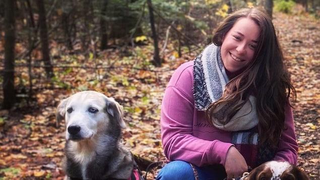 Alexandra Pineault est accroupie auprès de deux chiens au milieu d'un sentier en forêt.