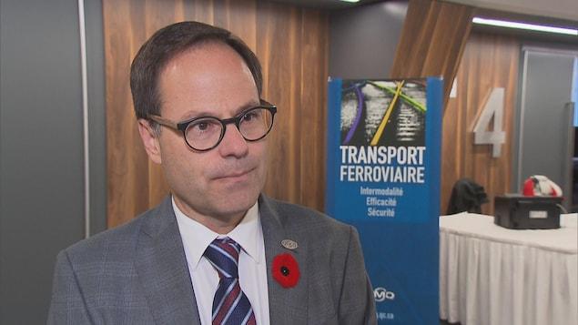 Alexandre Cusson à l'hôtel Delta de Trois-Rivières devant une bannière du forum