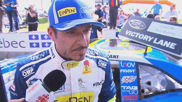 Le pilote Alex Tagliani avec un casquette bleu, devant sa voiture répond aux questions des journalistes