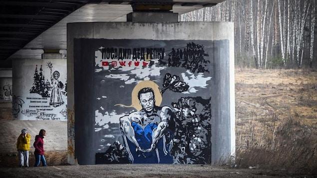 Deux personnes passent devant l'immense murale peinte sur l'un des piliers d'un viaduc.