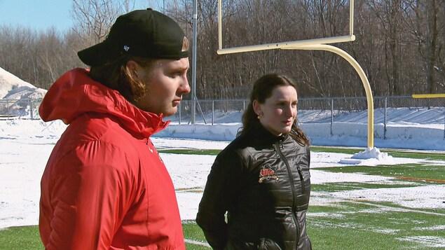 Deux athlètes discutent sur un terrain synthétique déneigé.